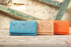 Colorful wallets on natural old wall background Royalty Free Stock Photos