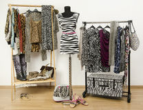 Colorful wardrobe with jungle pattern clothes and accessories. Stock Photography