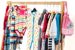Dressing closet with kids clothes arranged on hangers. royalty free stock images