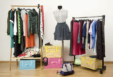 Colorful wardrobe with polka dots clothes and accessories. Dressing closet with polka dots clothes arranged on hangers and an outfit on a mannequin stock image