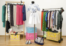 Colorful wardrobe with polka dots clothes and accessories. Dressing closet with polka dots clothes arranged on hangers and an outfit on a mannequin stock photography