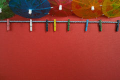 Colorful washline with clothespins and paper umbrellas, copy spa Royalty Free Stock Photography
