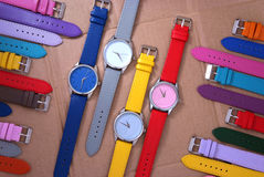 Colorful watches on cardboard background Royalty Free Stock Photo