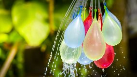 Colorful water balloons play in plastic swimming pool stock photography