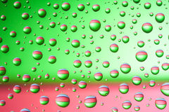 Colorful water drops. Bright water drops above green and red colors Royalty Free Stock Images