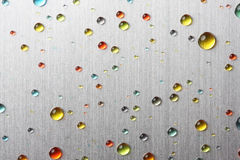 Colorful water drops on metal Stock Photography