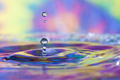 Colorful water drops and splash. Colorful red, yellow, pink green and blue water drop and splash with reflections of tie dyed fabric in background and drop Royalty Free Stock Photography