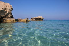 Colorful water of Konnos Bay in Cyprus with rocks and stones. The view to crystal clear colorful water of Konnos Bay in Cyprus with stones, rocks and a visible Stock Photo