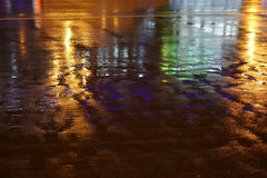 Colorful water reflection on the road. Night city lights reflected in puddle. Royalty Free Stock Images