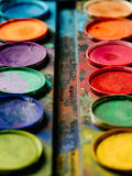 Colorful watercolor paint palette. Photo of a palette of watercolor paints on a well-used tray Royalty Free Stock Image