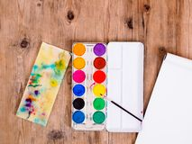 Watercolor paints and drawing pad on a brown wooden table, top view stock images