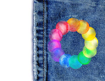 Colorful watercolor splashes on jeans background. Denim jeans background with round frame made of watercolor rainbow blobs. Watercolor frame with colorful Stock Image