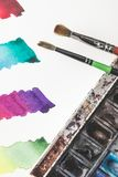 Colorful watercolor strokes in drawing album, paints and paintbrushes Stock Photo