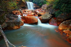 Colorful waterfall in forest. Scenic view of colorful waterfall reflecting Autumn colors in forest with slow motion blur effect Stock Photo