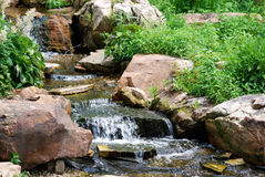 A colorful waterfall with greenery in Lincoln Park Zoo. A waterfall with brown rocks and greenery flowing in Lincoln Park Zoo Chicago, Illinois Stock Photo