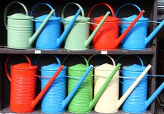 Colorful watering cans. Rows of colorful watering cans Royalty Free Stock Photography