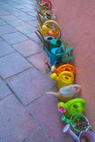 Colorful watering cans. Colorful row of watering cans on the stone floor Royalty Free Stock Photography