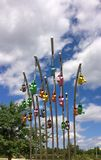 Colorful watering cans suspended above the ground Stock Photos