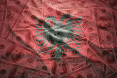 Colorful waving albanian flag on a dollar money background. Colorful waving albanian flag on a american dollar money background stock photos