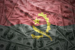 Colorful waving angolan flag on a dollar money background Royalty Free Stock Photos