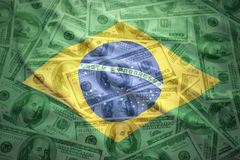 colorful waving brazilian flag on a dollar money background Stock Image