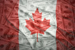 Colorful waving canadian flag on a dollar money background Royalty Free Stock Photos