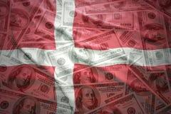 Colorful waving danish flag on a dollar money background. Colorful waving danish flag on a american dollar money background Royalty Free Stock Photo