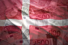 Colorful waving danish flag on a euro  background. Colorful waving danish flag on a euro money background Royalty Free Stock Photo