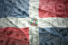 Colorful waving dominican republic flag on a dollar money background. Colorful waving dominican republic flag on a american dollar money background stock image