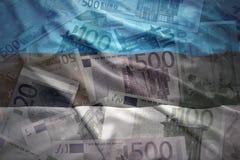 Colorful waving estonian flag on a euro  background. Colorful waving estonian flag on a euro money background Stock Image