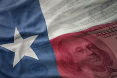 Colorful waving flag of texas state on a american dollar money background. Royalty Free Stock Images
