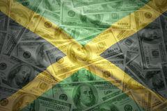 Colorful waving jamaican flag on a dollar money background. Colorful waving jamaican flag on a american dollar money background royalty free stock photography
