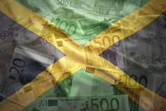 Colorful waving jamaican flag on a euro background. Colorful waving jamaican flag on a euro money background royalty free stock image