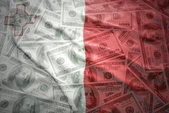 Colorful waving maltese flag on a dollar money background. Colorful waving maltese flag on a american dollar money background Stock Photo