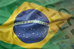Colorful waving national flag of brazil on a euro money banknotes background. Stock Photography