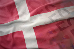 Colorful waving national flag of denmark on a euro money banknotes background. Finance concept Royalty Free Stock Photo