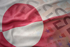 Colorful waving national flag of greenland on a euro money banknotes background. Royalty Free Stock Photography