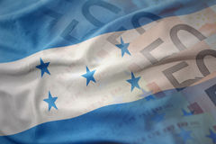 Colorful waving national flag of honduras on a euro money banknotes background. Royalty Free Stock Image