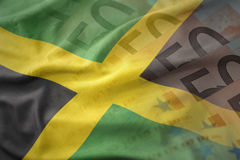 Colorful waving national flag of jamaica on a euro money banknotes background. Royalty Free Stock Images