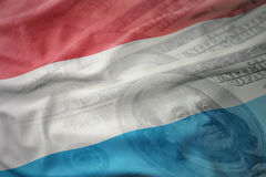 Colorful waving national flag of luxembourg on a american dollar money background. Finance concept Stock Images