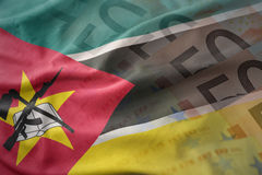 Colorful waving national flag of mozambique on a euro money banknotes background. Stock Photos
