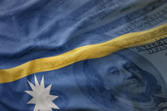 Colorful waving national flag of Nauru on a american dollar money background. Royalty Free Stock Photos