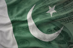 Colorful waving national flag of pakistan on a american dollar money background. Finance concept Stock Photography