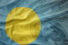 Colorful waving national flag of Palau on a american dollar money background. Stock Photography