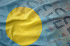 Colorful waving national flag of Palau on a euro money banknotes background. Stock Photography