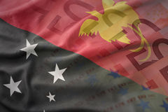 Colorful waving national flag of Papua New Guinea on a euro money banknotes background. Stock Photo