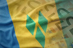 Colorful waving national flag of saint vincent and the grenadines on a euro money banknotes background. Stock Photos