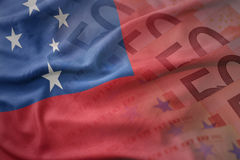 Colorful waving national flag of Samoa on a euro money banknotes background. Royalty Free Stock Images