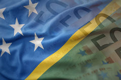 Colorful waving national flag of Solomon Islands on a euro money banknotes background. Stock Photography