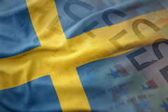 Colorful waving national flag of sweden on a euro money banknotes background. Finance concept Stock Image